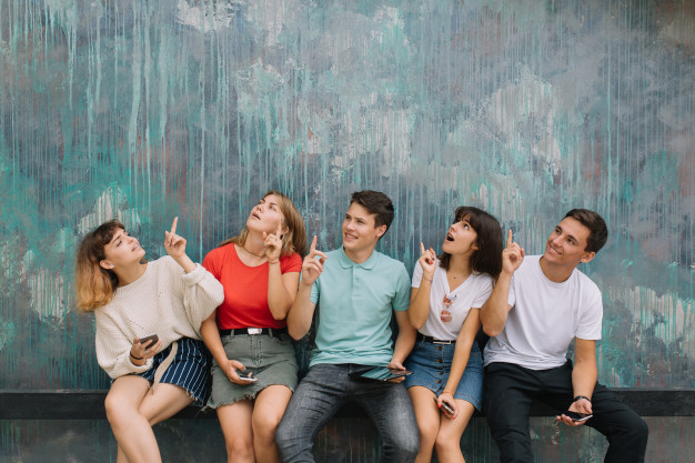 happy-group-teenagers-show-something-vintage-background-copy-space_1429-4598